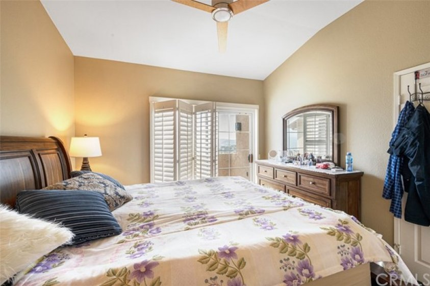 Master bedroom with private balcony, ceiling fan, and plantation shutters.