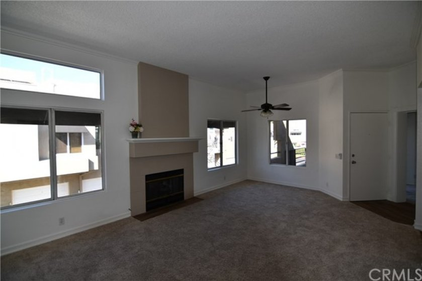 Living room and dining area. Note the 9.5'+ height of the ceilings. The entire unit has been freshly painted. Upgraded wood mantle on the fireplace. Upgraded fan w/light kit. Again, dual pane windows. All new carpet. Laminate flooring in the entry.