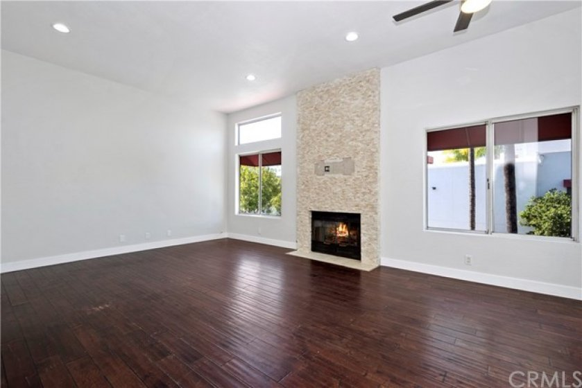 Great room features stacked stone fireplace and wood floors