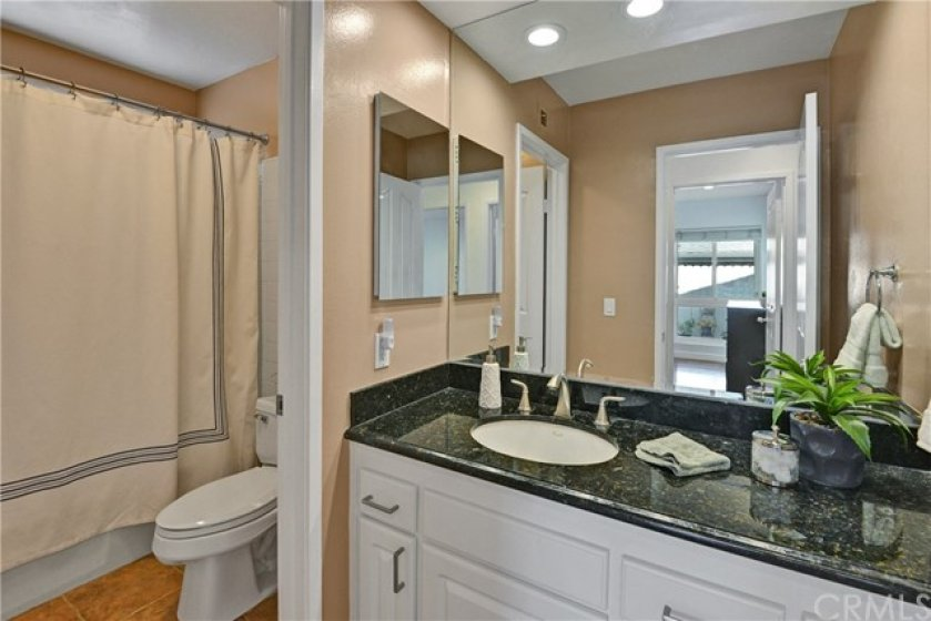 Full hall bathroom with granite counters and recessed lighting.