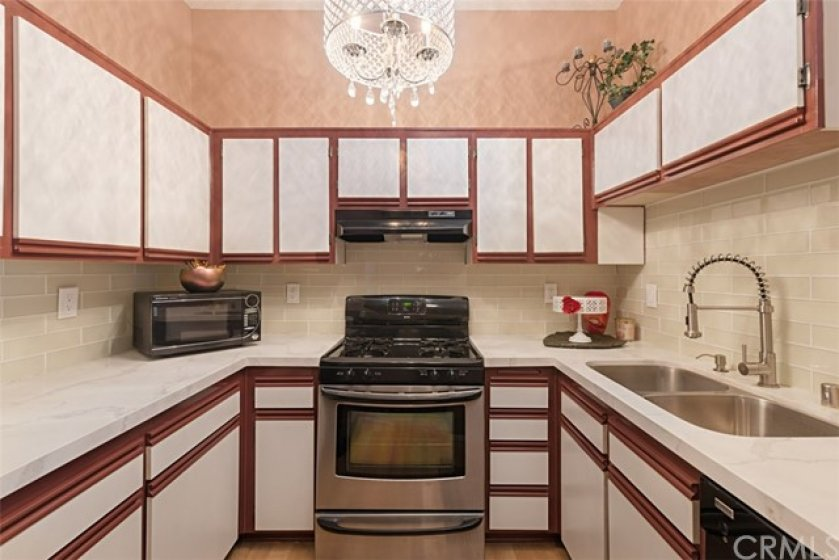 Beautiful, b right kitchen ... updated glass tile back splash, high-quality quartz counters and two-tone cabinets, newer appliances.