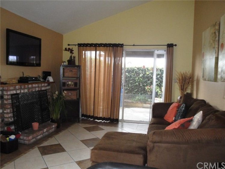 Living area with vaulted ceilings, gas fireplace and sliding door that leads to large patio area.