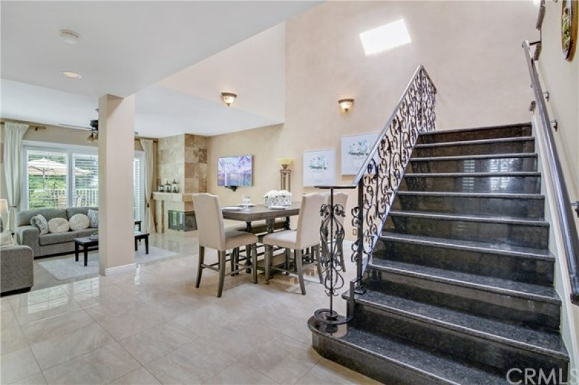 Beautiful porcelain tile flooring and a stone staircase with an intricate wrought iron railing are just a few of the upgrades in this home.