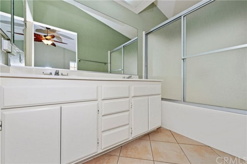 Master bathroom with dual sinks, lovely neutral tile flooring and a separate water closet.