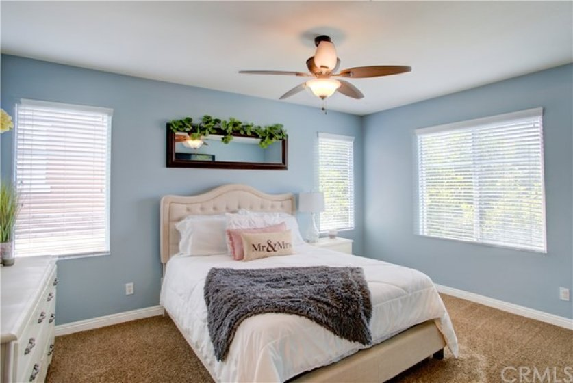 Master bedroom at end of hall has natural light and ceiling fan.