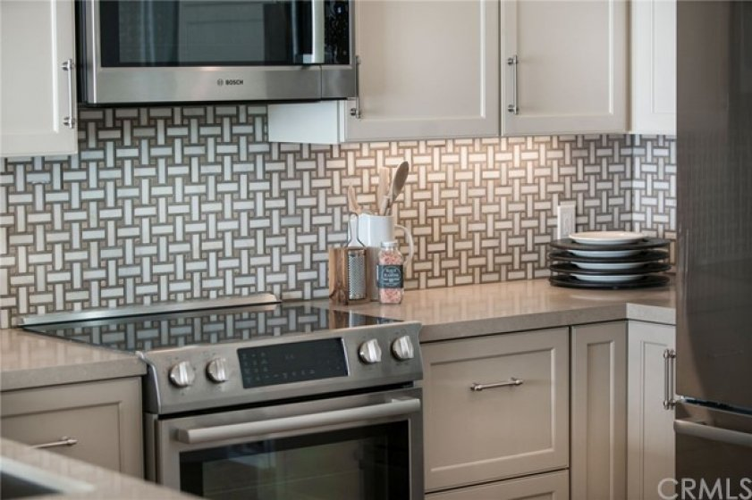"""Mosaic tile backsplash compliments the clean, hard surface work space.  All doors are """"soft-close."""""""