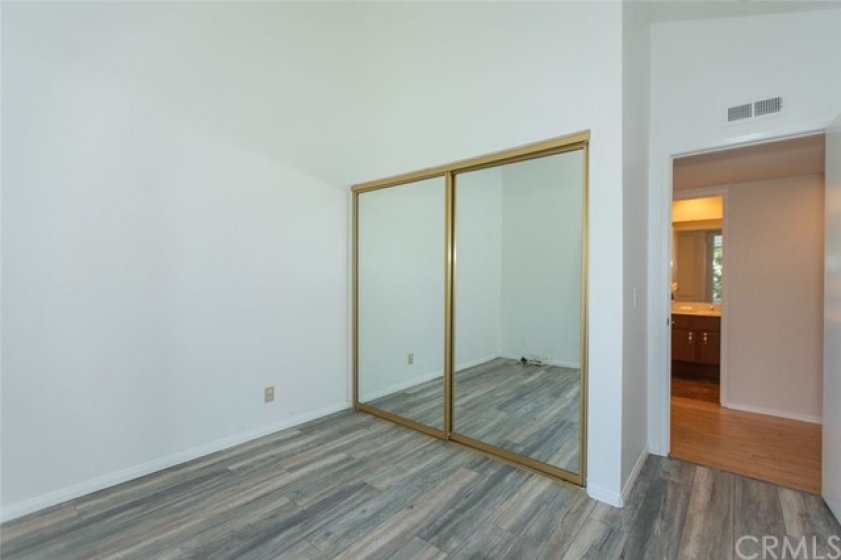 Bedroom with new flooring and mirrored closet.