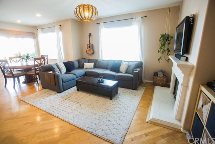 The spacious living room and adjacent dining room feature a lovely floor, large windows with treatment and recessed lighting.