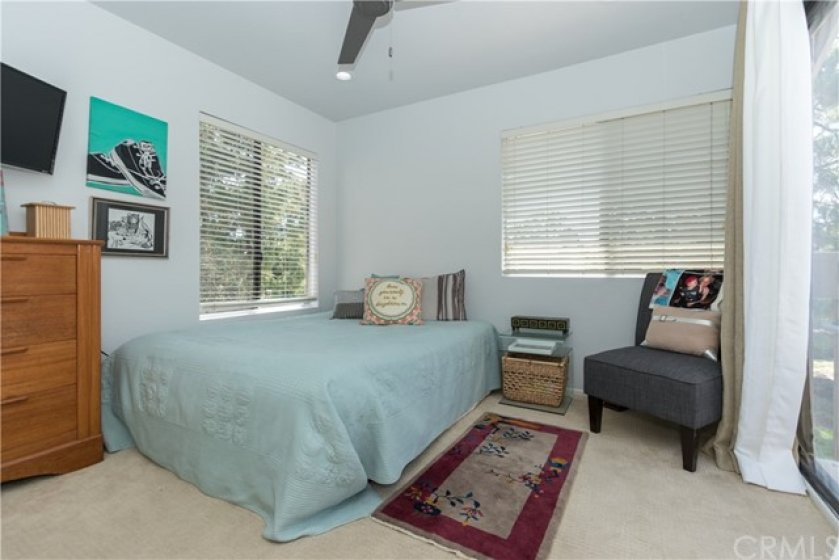 Sunny secondary bedroom with a ceiling fan.