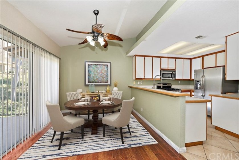 Lovely dining room adjacent to the kitchen and living room for an open concept.  Boasting beautiful wood flooring, an upgraded ceiling fan and upgraded moldings.  The balcony is perfectly located to enjoy dining al fresco or take in the beautiful SoCal weather with your morning coffee. Virtually staged.
