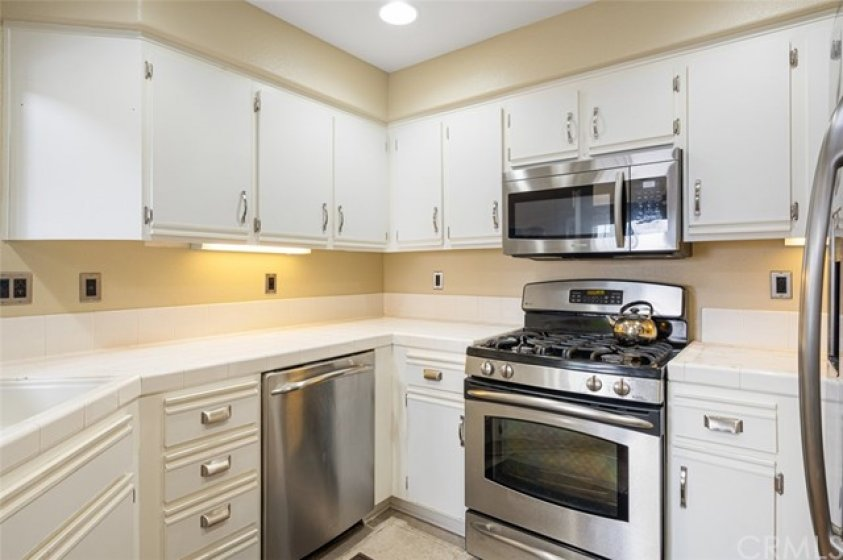 Updated kitchen with white cabinets, stainless steel appliances, and recessed lighting.