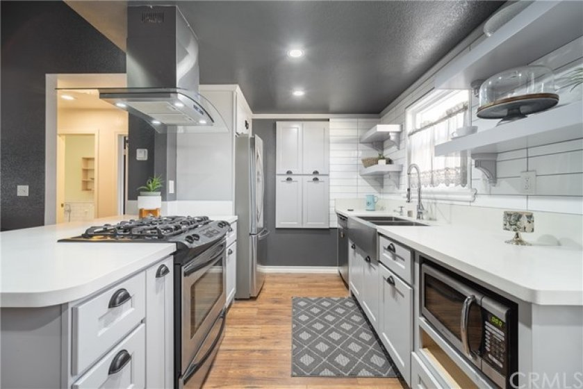 Newer kitchen cabinets with sparkling quartz counter tops opening up to the living room.