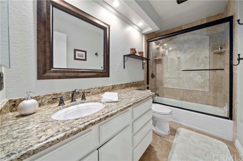 Hall bath with custom tile tub surround and granite topped vanity.  Ceramic tile on the floor