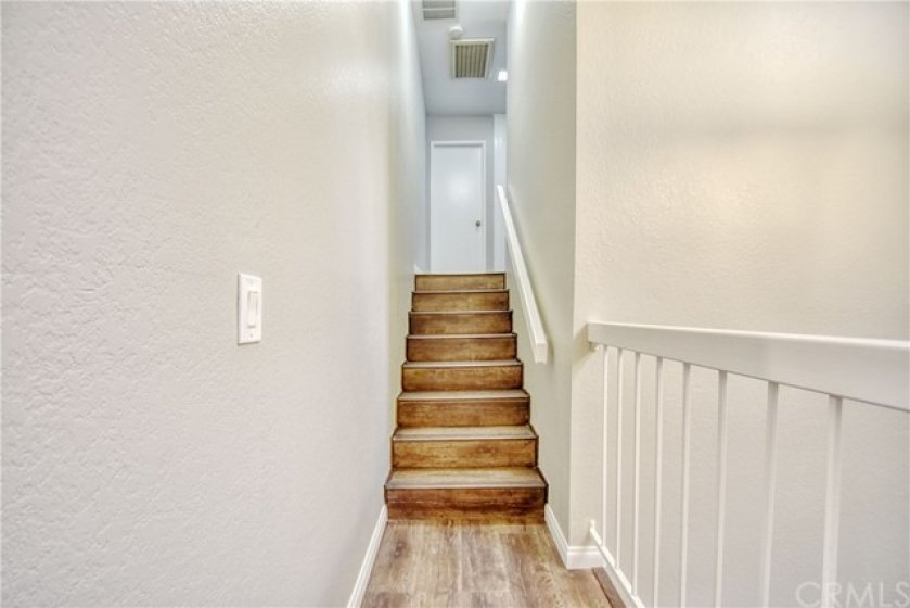 Stairs going up to second level where two guest bedrooms and a full bathroom are located.