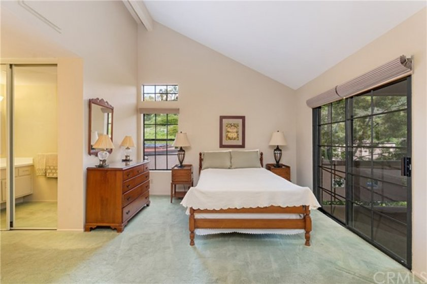 Bedroom also has vaulted ceiling and sliding glass doors to the balcony.