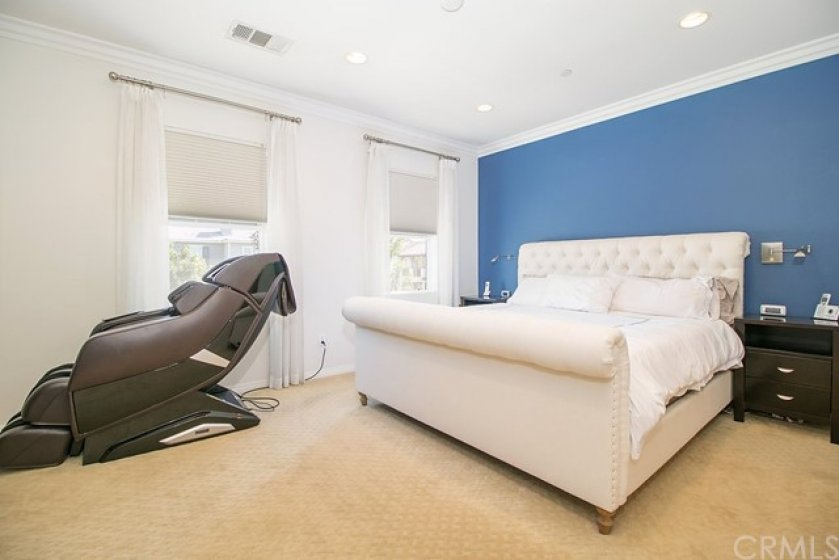 The spacious master bedroom has upgraded carpet, recessed lighting and custom drapes.