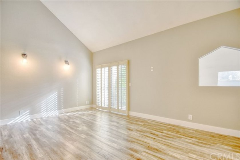 Master suite with vaulted ceiling and laminate flooring.
