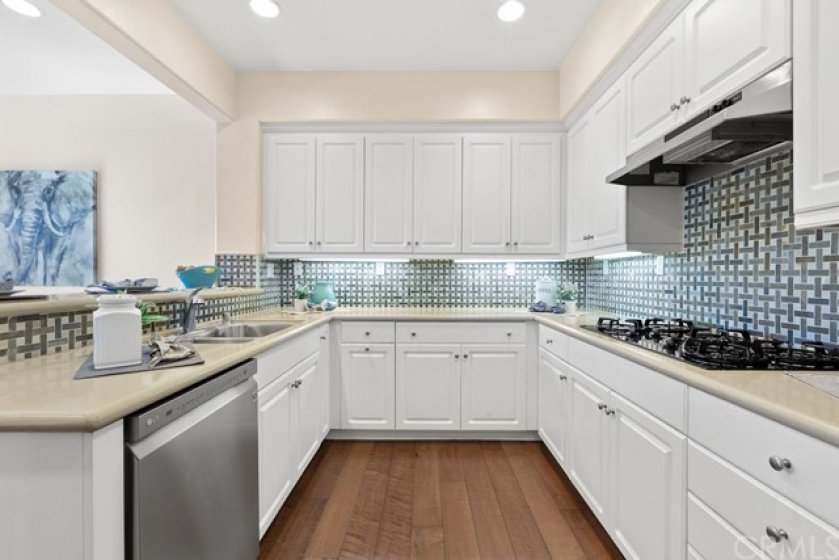 Beautiful backsplash, stainless appliances. well designed layout and tons of gleaming white cabinets in this kitchen will please the most discerning home chef.