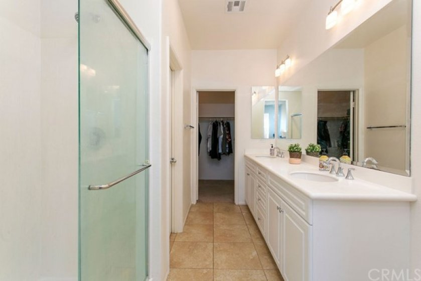"r suite Bathroom with oversize shower with glass slider, 18"" tile flooring, double sink vanity & large walk in closet."