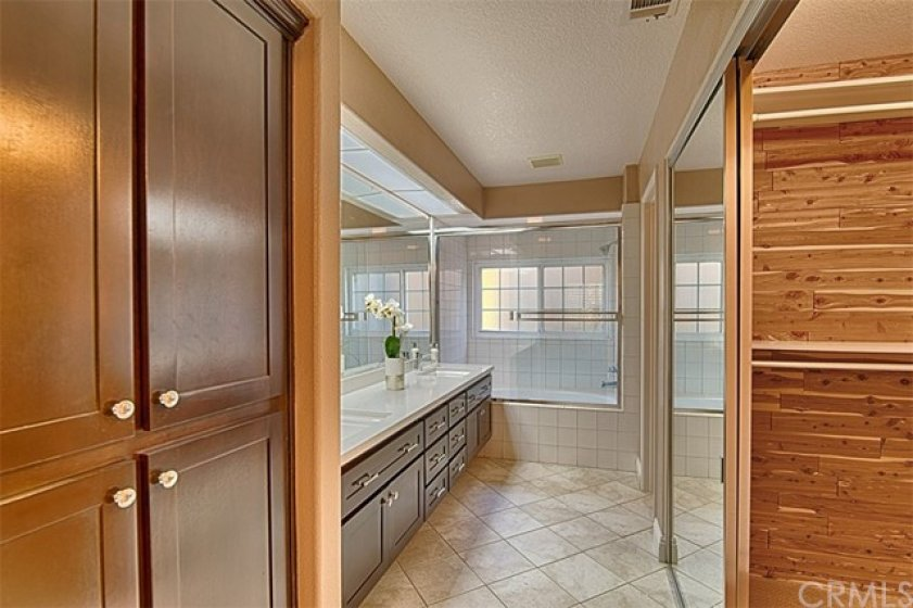 Master bath with linen storage on the left and the mirrored walk in closet on the right.