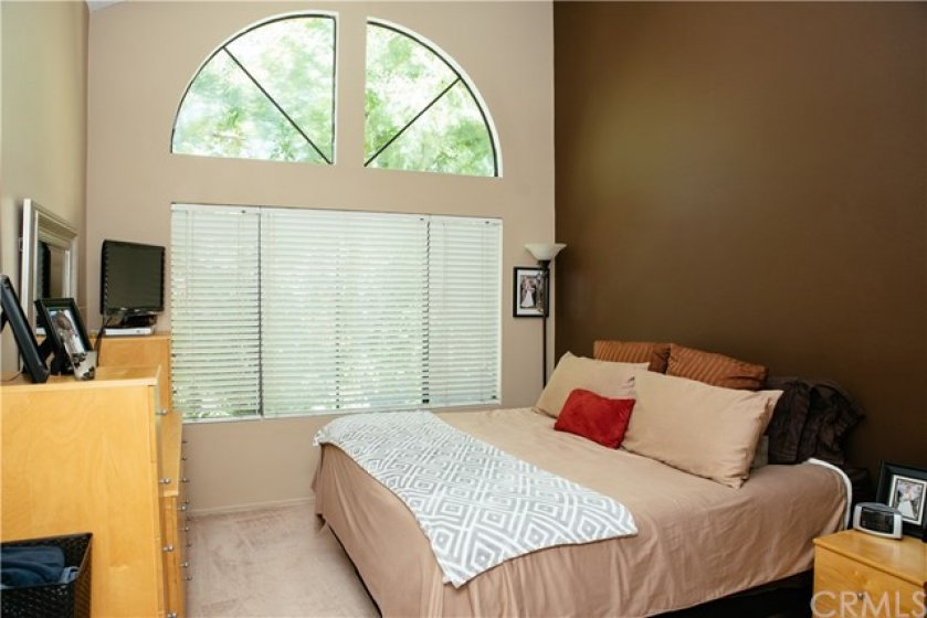 Master bedroom brings in lots of natural light with custom designed transom windows and picture window below plus custom wall paints.