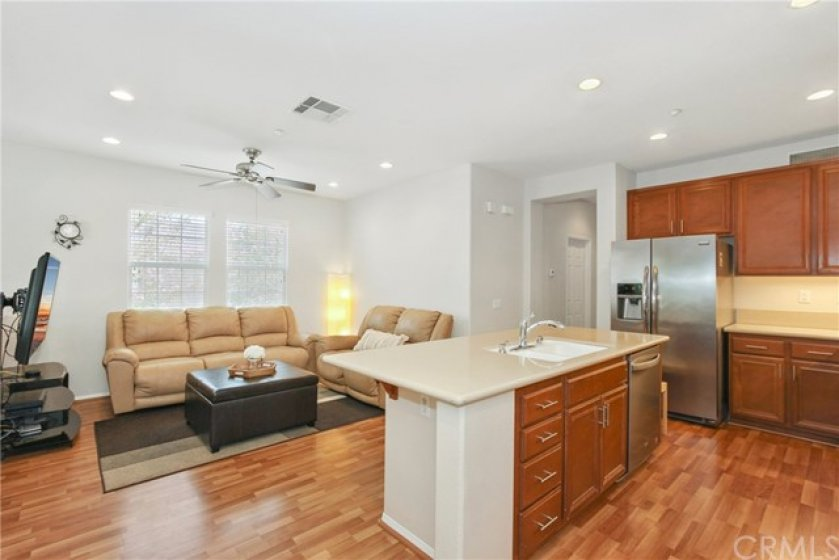 Beautiful laminate floors, recessed lights, and large center island with quartz countertop