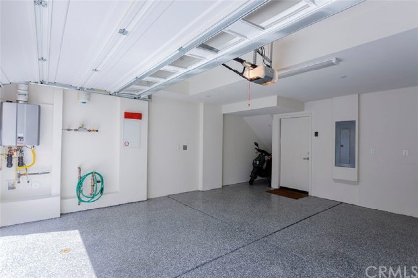 The garage with epoxy flooring and tankless water heater.