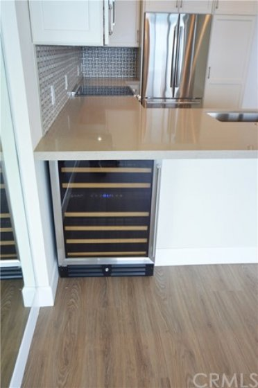 Under-counter wine cooler is convenient to the kitchen and living room.