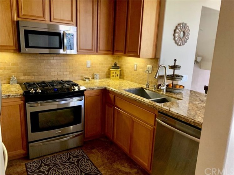 KITCHEN WITH STAINLESS APPLIANCES AND GRANITE COUNTER TOPS