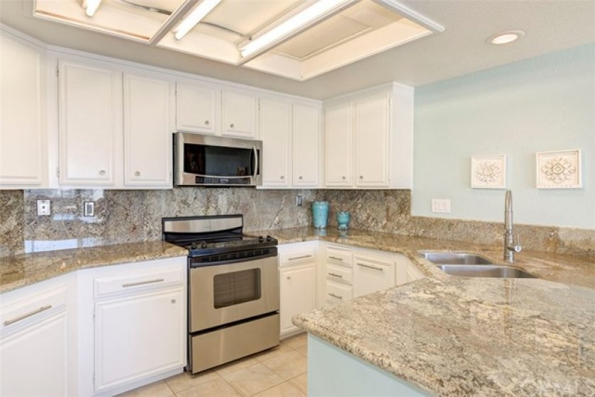 Light and Bright Kitchen, beautiful Granite Counter Tops and Backsplash, Stainless Appliances and white cabinetry