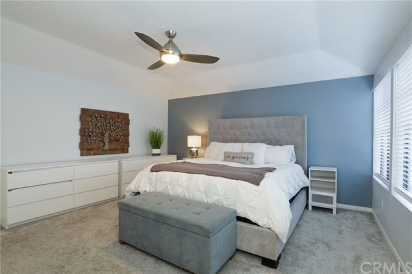 Gorgeous master bedroom with ceiling fan and custom paint