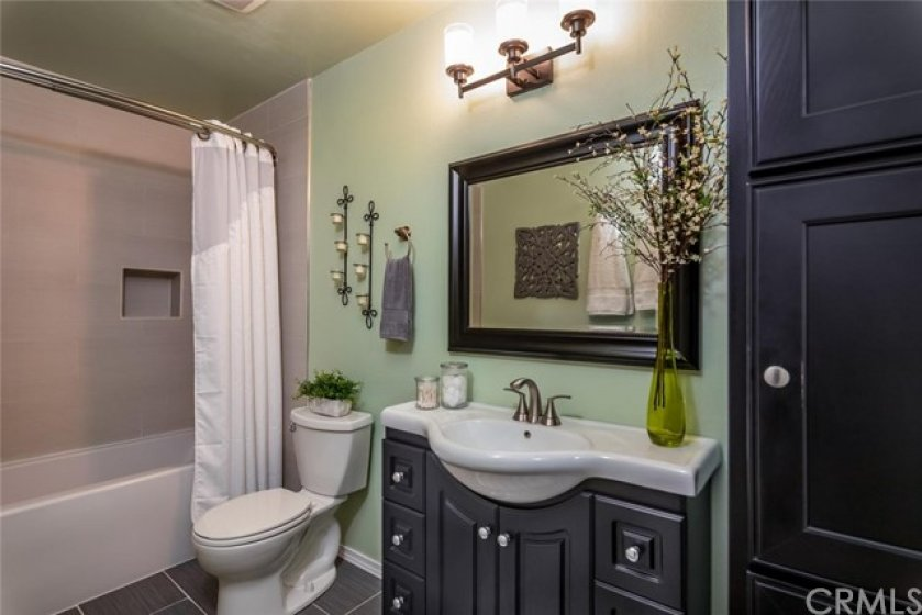 Updated bath features newer tub, tile flooring, vanity and linen storage.