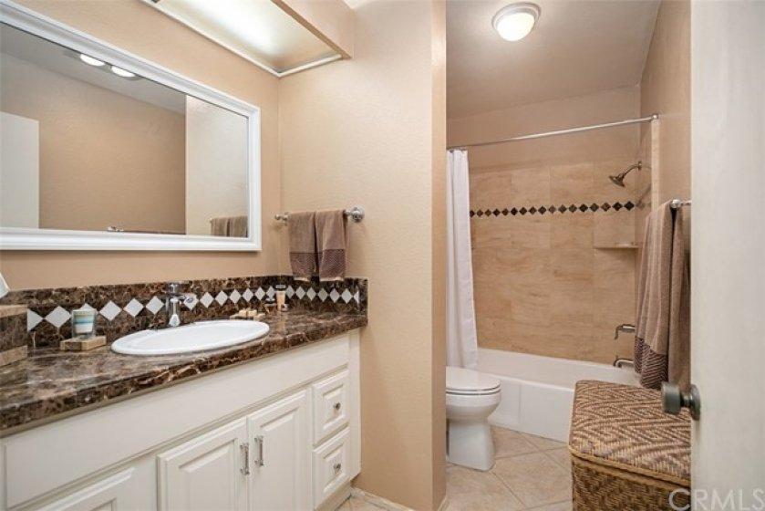 Secondary bathroom with granite tile vanity
