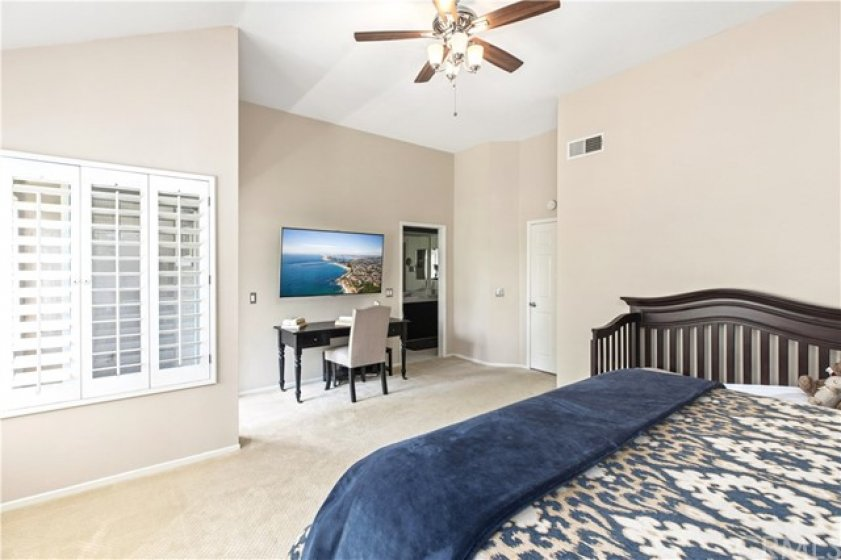 The master suite is very spacious, with shutters on the windows.