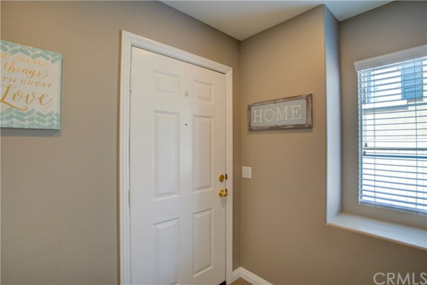 Entry door opens to foyer with door to garage, closet and stairs to living space.