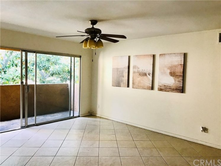 Spacious Living Room with Tile Flooring, Ceiling Fan with Light and Nice Patio with view of beautiful tree.