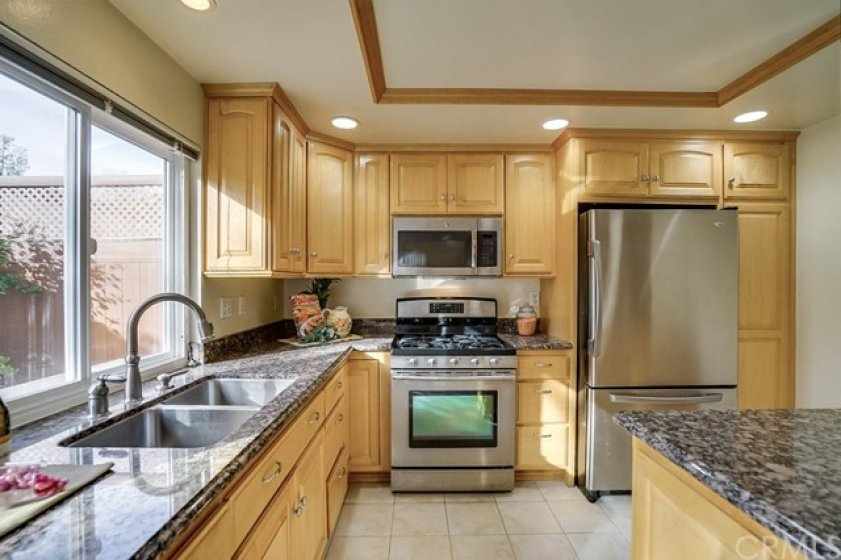 Remodeled kitchen with light wood cabinetry, granite counters and stainless steel appliances