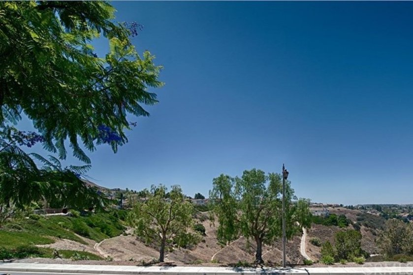 Condo overlooks open canyon area with hills and city lights view