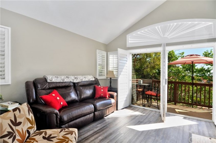 Living room with private patio entry level main floor featuring custom shutters.