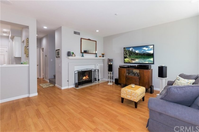 Lives large - nice living room with cozy fireplace and mantle - soft grey colors are relaxing after a day out in the world...laminate flooring is easy care so more time to relax!