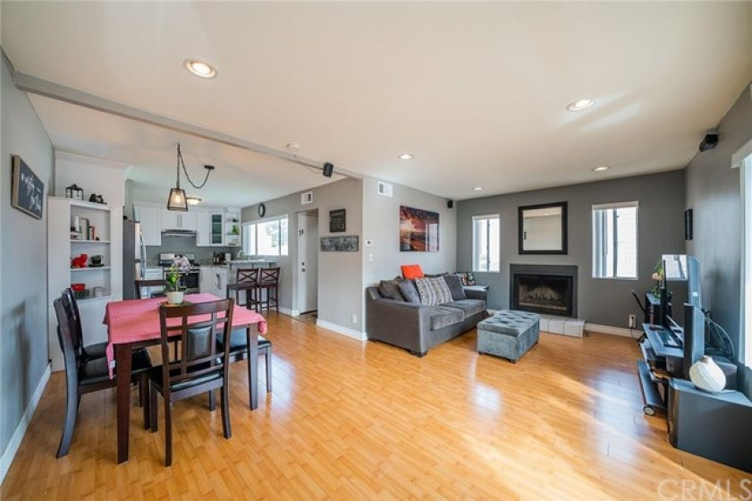 Great view of the opened floor plan, showing recess lights, fire place and kitchen with the small island.