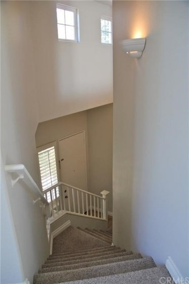 Staircase coming up from the entry and garage