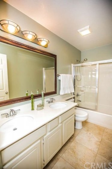 Large upstairs hall bath with dual vanities and a large tub/shower combo