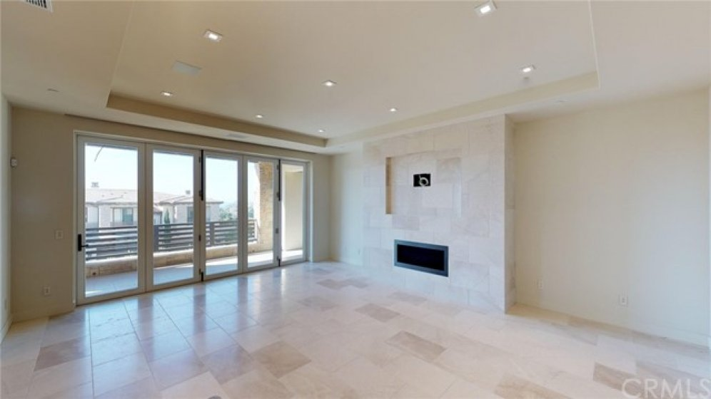 Great room linear fireplace with tile accent wall for television.