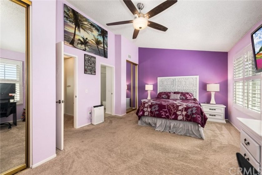 Large room with ceiling fan, and dual mirrored closets.