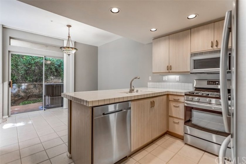 The kitchen features a breakfast bar area as well as Samsung stainless steel appliances, including a 5 burner range!