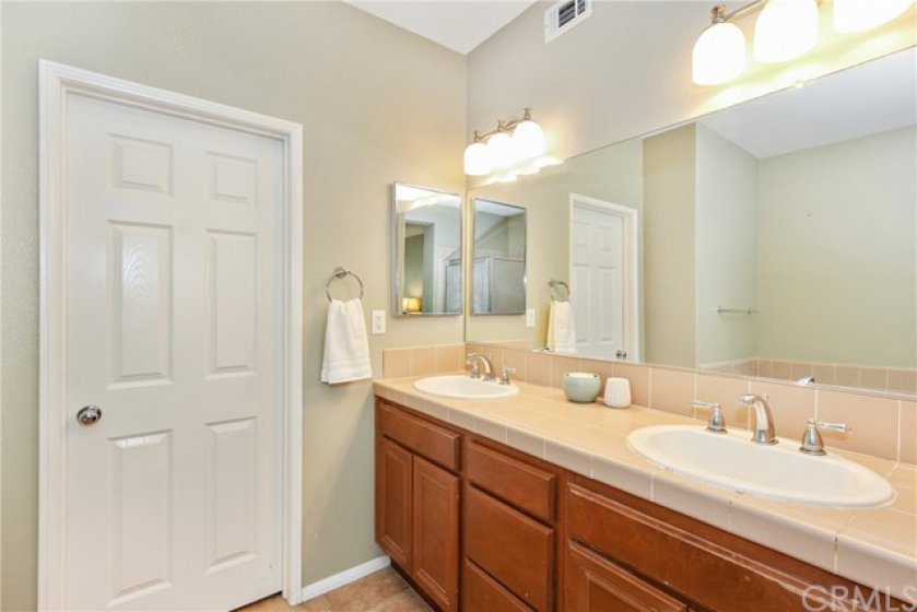 Master bath features a walk-in closet & dual vanity with new light fixtures