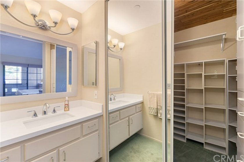 Mirrored wardrobe doors open to a large Cedar-lined, walk-in closet.