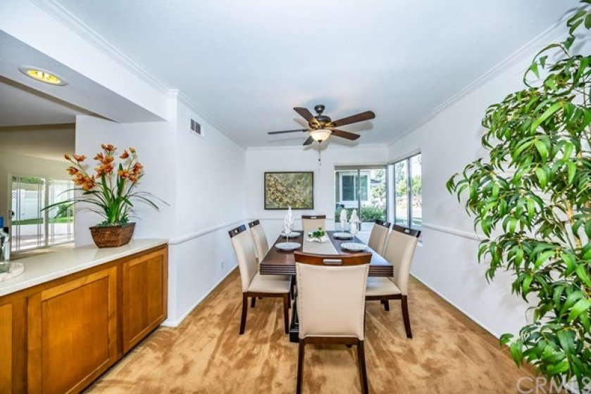 Fabulous dining room with a ceiling fan and remodeled credenza.