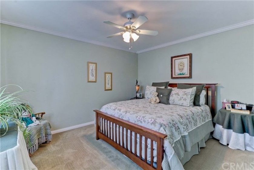 Secondary bedroom with ceiling fan and crown molding.